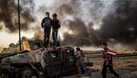 Fight for Mosul. Taha Sirhan, 11, carrying the Iraqi flag through burned out oil fields in the city of Qayyarah south east of Mosul in Iraq. His dad was killed by ISIS during the occupation because he was working for the Iraqi police. Foto: Asger Ladefoged.